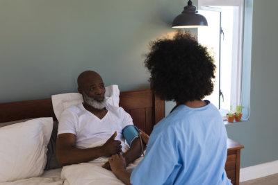 caregiver checking the blood pressure of senior man