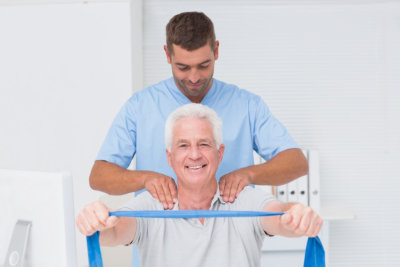 caregiver assisting senior man in exercise
