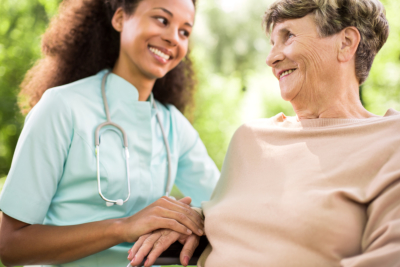 Young nurse is holding elder woman s hand